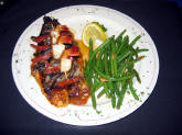 Blackened Fish served on a bed of roasted roma tomatoes and topped with red bell peppers, portobello mushrooms and shrimp.